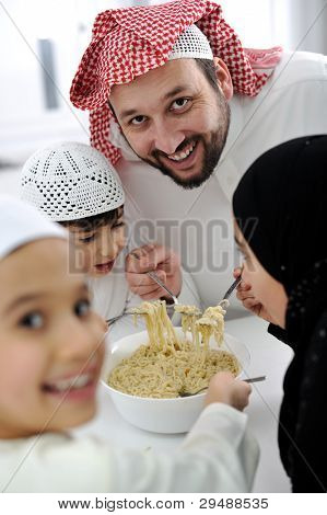 Arabic muslim family eating  at home together, father and kids