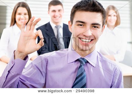Portrait of business man showing ok sign with cheerful team in background