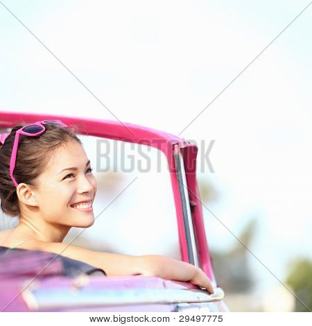 Car woman smiling happy enjoying car road trip travel vacation. Young retro woman in pink vintage convertible car looking to side. Beautiful young multiracial caucasian / chinese asian in Havana, Cuba