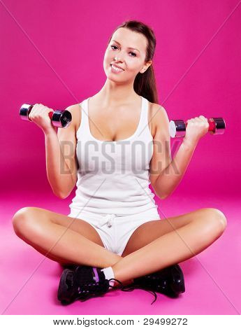 beautiful young  woman with dumbbells,  against pink studio background