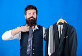 Adding A Tie To His Look. Hipster Matching Silk Necktie To His Bearded Face. Brutal Hipster Holding  poster