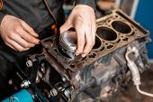 Close-up Car Mechanic Holding A New Piston For The Engine, Overhaul.. Engine On A Repair Stand With  poster