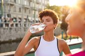 Young african woman drinking water after jogging. Athlete girl resting while drinking water after wo poster