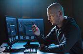 cybercrime, hacking and technology concept - male hacker with smartphone and progress loading bar on poster