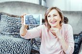 Attractive Woman Laughs While Taking Selfie On The Back Camera Of Her Phone. Mature Woman Smiles Whi poster