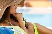 stock photo of woman body  - Beautiful young woman lying on deckchair by swimming - JPG