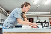 Woman cutting signs or vinyl wraps producing advertising materials in workshop of agency poster
