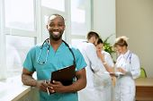 Healthcare People Group. Professional African American Male Doctor Posing At Hospital Office Or Clin poster