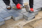 Hands of worker installing concrete paver blocks with rubber hammer poster