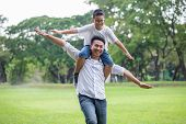 Happy Asian Family .father And Son Runing , Playing And Stretching Out Hands Together In The Park .  poster