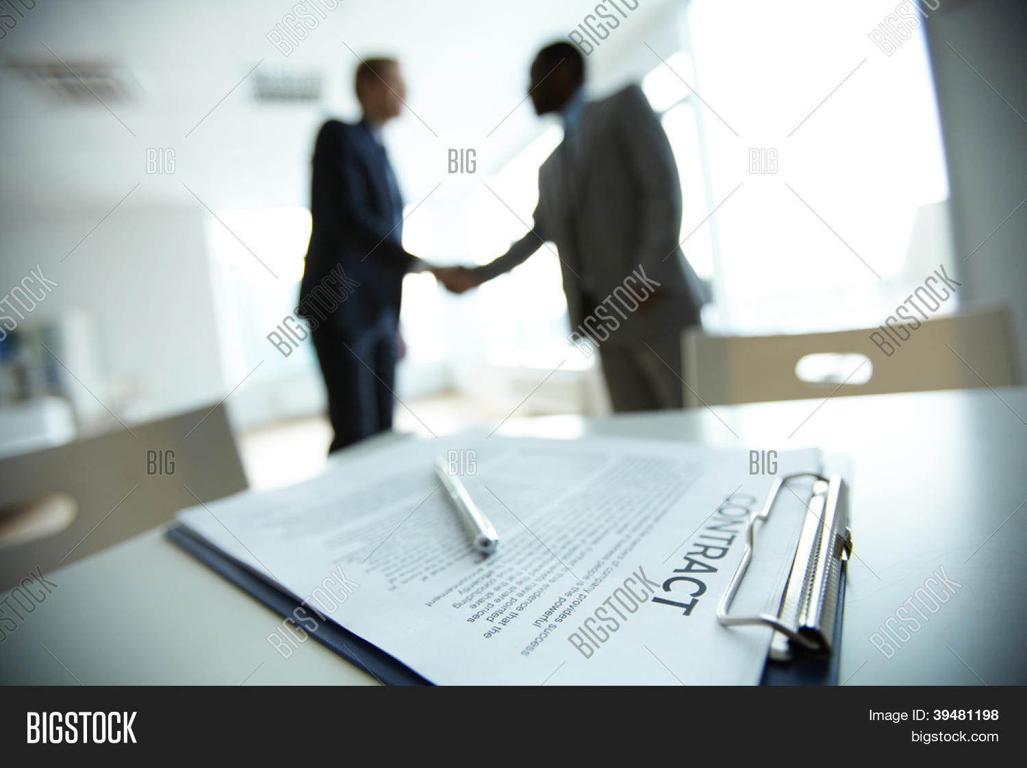 Image of business contract on background of two employees – Business Contract