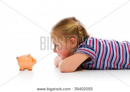 Little girl with piggy bank. Studio shot.