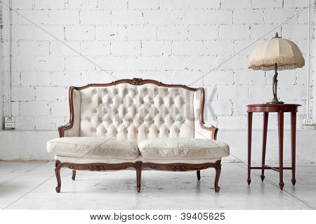 White genuine leather classical style sofa in vintage room with desk lamp
