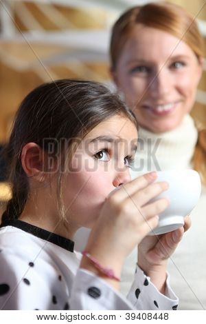 Little girl drinking from breakfast bowl
