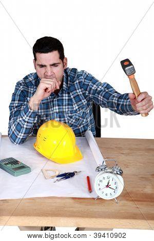 Architect smashing alarm with hammer