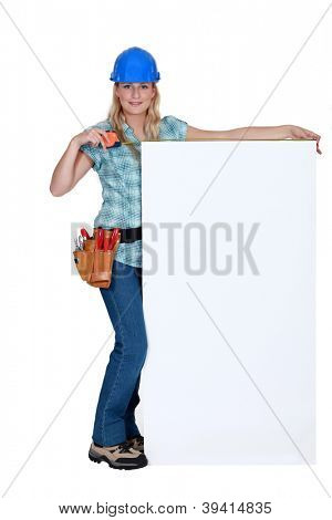 Tradeswoman standing next to a blank sign
