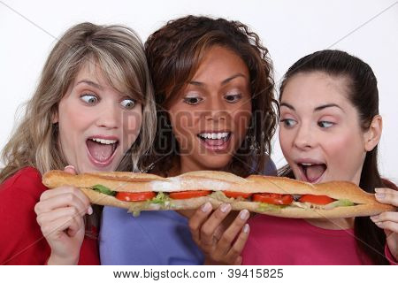 A group of friends eating a long sandwich