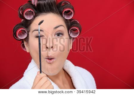 Brunette wearing hair roller and white bath robe