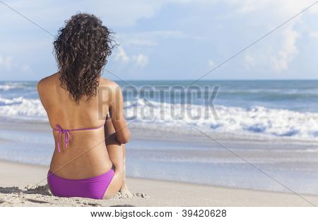 Rear view of a sexy young brunette woman or girl wearing a bikini sitting on a deserted tropical beach with a blue sky