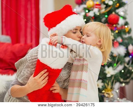 Mother Kissing Baby Taking Out Present From Christmas Sock