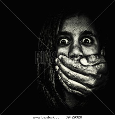 Horror portrait of a very frightened girl with an adult hand covering her mouth isolated on a white background