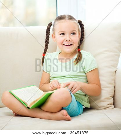 Cute little girl is reading book while sitting on a couch, indoor shoot