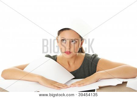 Sad overworked woman with papers sitting at the desk. Tired and exhausted business woman.