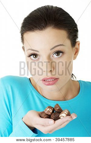 Young beautiful woman in casual clothes with hand full of chocolates