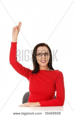 Young woman sitting at the desk raising her hand knowing the answer