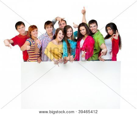 Happy young group of people standing together and holding a blank sign for your text