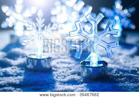 transparent glowing snowflakes on snow, blue toned