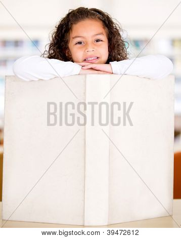 Happy schoolgirl with a book at the library
