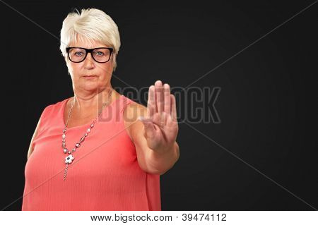 portrait of a senior woman showing stop sign on black background