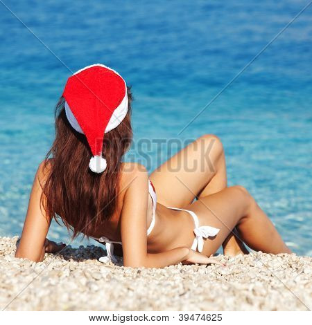 Young woman in santa hat sitting on the beach. Christmas vacation