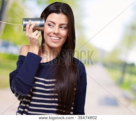Female Holding A Metal Tin As A Telephone, Outdoor