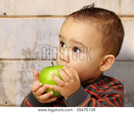 Portrait Of Baby Boy Eating Green Apple against an old rusty wall