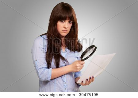 Portrait Of A Girl Holding A Magnifying Glass And Paper On Grey Background