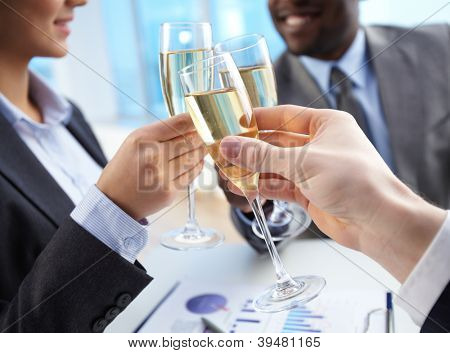 Close-up of business partners hands cheering up with flutes of golden champagne