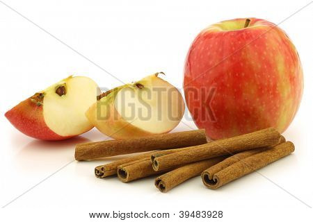 dried cinnamon sticks, a fresh apple and some cut pieces on a white background