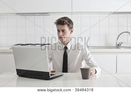 A young man in tie is holding a cup while is using a laptop computer