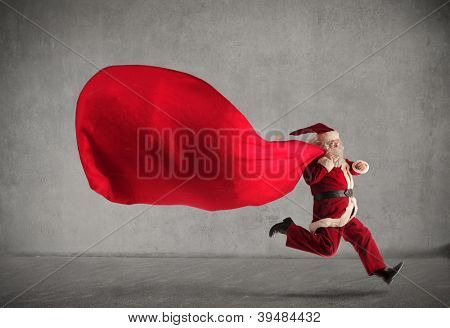 Santa Claus running with a very big sack full of presents