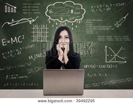 Estudiante de miedo frente a la prueba en línea con el ordenador portátil