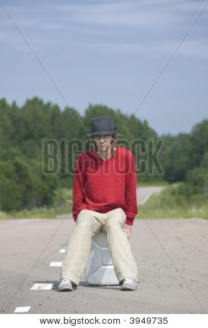 Young Man Sitting On Empty Gas Can