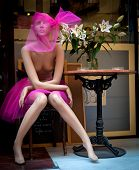 Old mannequin in pink gauze sitting by an old caf�© table