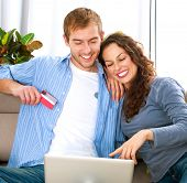 Family Shopping Online .Happy Smiling Couple Using Credit Card to Internet Shop on-line. Couple with