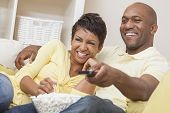 picture of watching movie  - A happy African American man and woman couple in their thirties sitting at home - JPG
