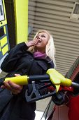 a young woman at a gas station gasoline tank. the cost of the car because of the gas prices are gett