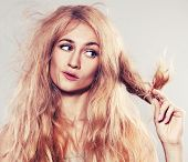 stock photo of split ends  - Young woman looking at split ends - JPG