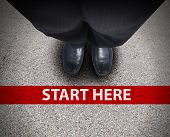 stock photo of saying  - A business man is looking down at his feet with a red race line that says start here to represent a journey - JPG
