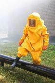 image of decontamination  - man in yellow chemical suit for cleaning operation - JPG